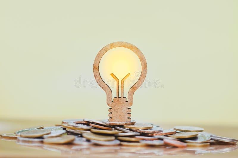 Bombilla y pila de monedas en el concepto de ahorros y de crecimiento del dinero o de reserva de la energía imagen de archivo