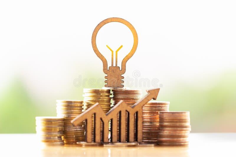 Bombilla y pila de monedas en el concepto de ahorros y de crecimiento del dinero o de reserva de la energ?a imagenes de archivo