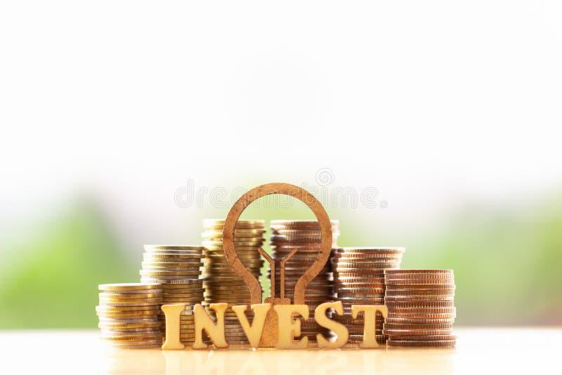 Bombilla y pila de monedas en el concepto de ahorros y de crecimiento del dinero o de reserva de la energ?a fotos de archivo
