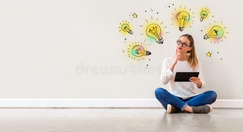 Bombillas de la idea con la mujer que usa una tableta fotos de archivo libres de regalías
