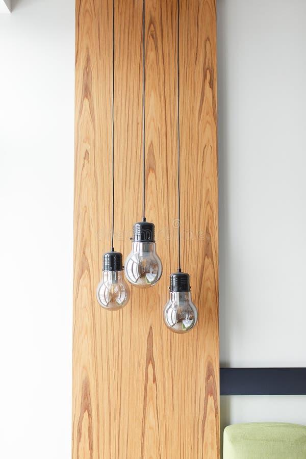 Bombillas en el fondo de madera del panel aislado en la pared blanca Decoración moderna del interior del dormitorio del estilo foto de archivo