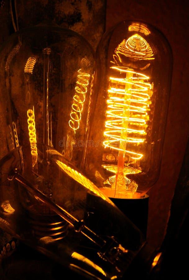 Bombillas incandescentes clásicas Cobbled de Edison con los alambres que brillan intensamente visibles en la noche imagen de archivo