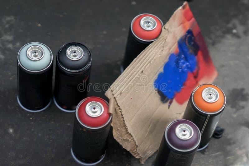 Bombolette spray della pittura di spruzzo e della tavolozza del cartone per pittura, graffito su un fondo scuro di asfalto Vista  fotografia stock libera da diritti