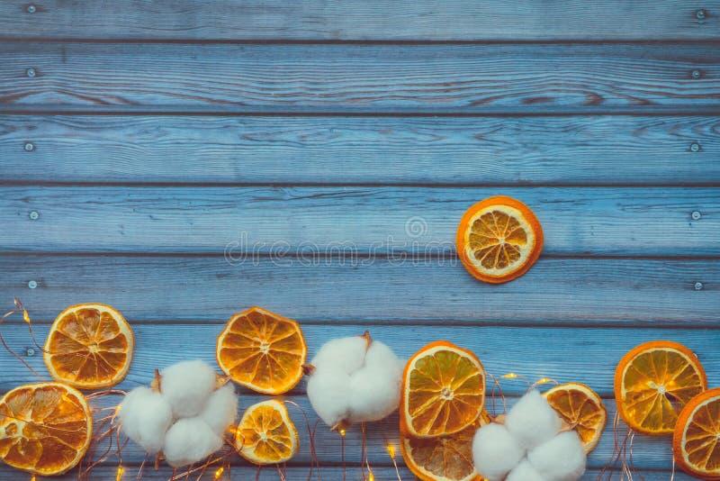 Bomullsfröhus och dired apelsiner på den blåa trätabellen fotografering för bildbyråer