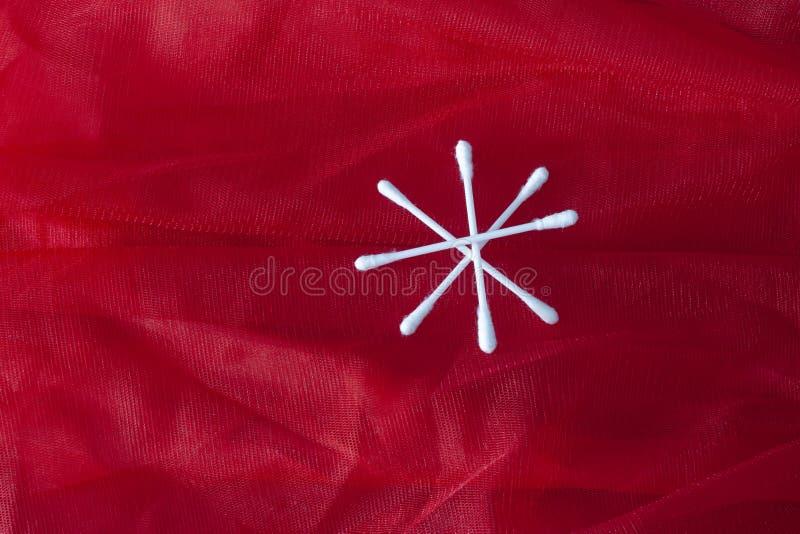 Bomullsknoppar som isoleras på röd bakgrund arkivfoton