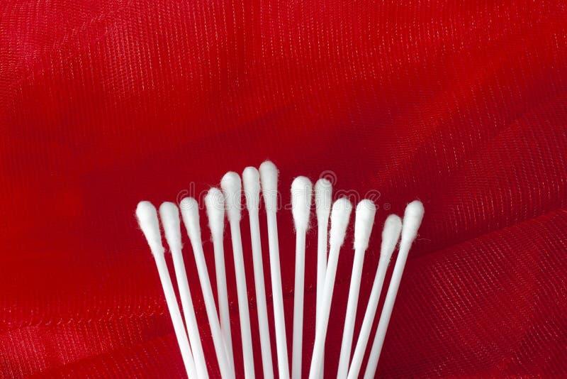 Bomullsknoppar som isoleras på röd bakgrund arkivfoto
