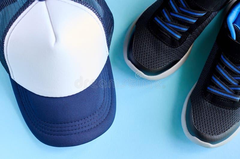 Boné de beisebol e sapatilhas na composição azul do fundo imagem de stock royalty free