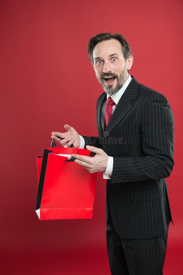 Bon achat Escompte choquant Homme d'affaires mûr tenant un sac en papier cadeau fond rouge Concept commercial Noël photo stock