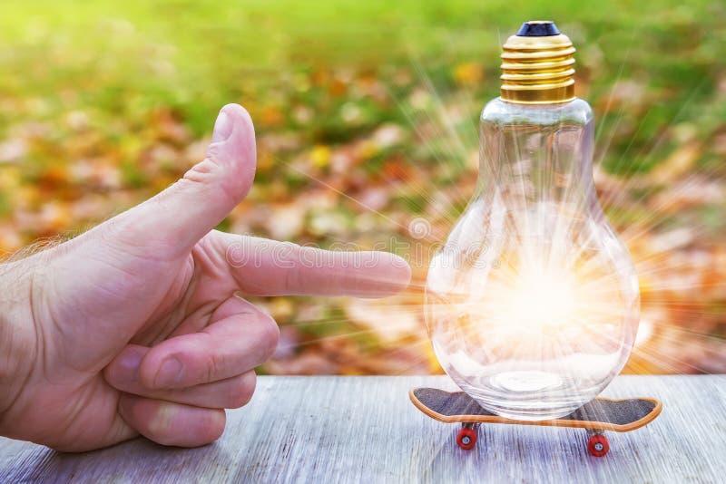 Bon concept d'idée le doigt indique l'ampoule rougeoyante qui est sur la planche à roulettes Solution de problème, idée, pensées  images libres de droits