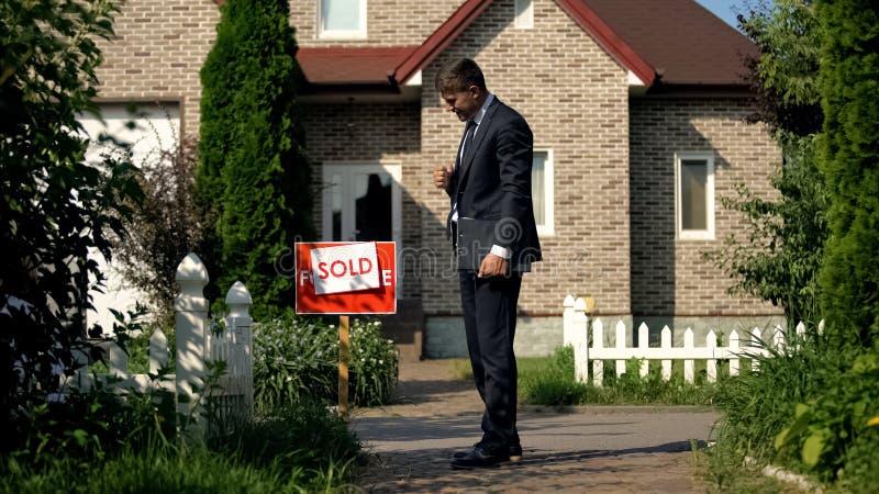 Bon gestionnaire immobilier regardant l'affichage vendu devant la maison, affaire photo libre de droits