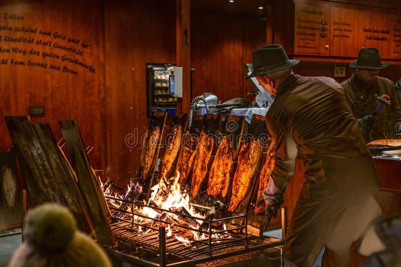 Bona Alemanha 17 12 2017 salmões ardidos deliciosos são fumado no fogo aberto no mercado do Natal fotos de stock royalty free