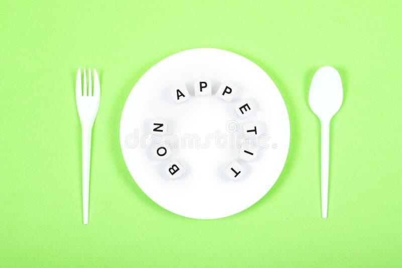 Bonappetittext på den runda vita plattan med skeden, gaffel på grön bakgrund Kokkonst matlagning, kök, restaurangmodell royaltyfri foto
