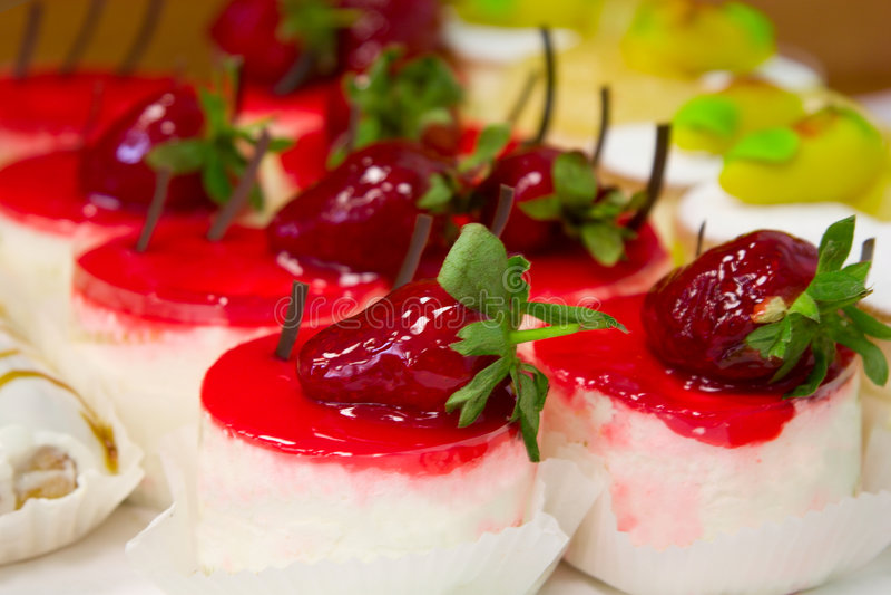 Bonbon backt mit strawberies unter Sahne zusammen lizenzfreie stockfotografie