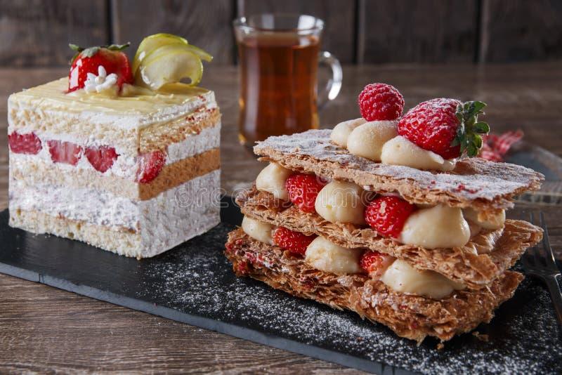 Bonbon crème à dessert de feuille de mille de givrage de fraise de gâteau sur la pierre noire photos stock