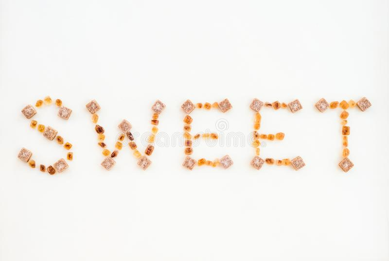 BONBON geschrieben mit brauner Zuckerstücken stockbild