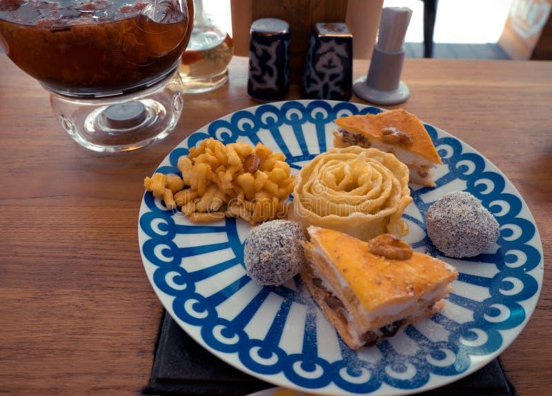 Bonbon-Klemme, Klemme und Nüsse auf der Platte mit blauen Dreiecken, das Konzept des Nachtischs lizenzfreie stockbilder