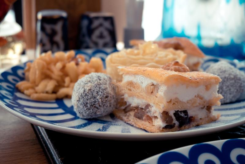Bonbon-Klemme, Klemme und Nüsse auf der Platte mit blauen Dreiecken, das Konzept des Nachtischs lizenzfreie stockfotos