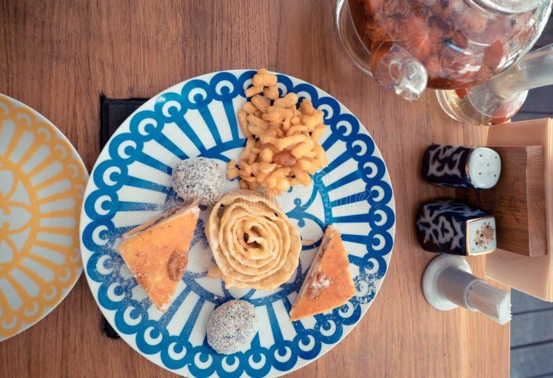 Bonbon-Klemme, Klemme und Nüsse auf der Platte mit blauen Dreiecken, das Konzept des Nachtischs lizenzfreie stockfotografie