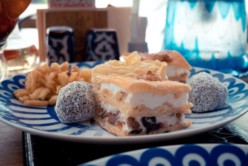 Bonbon-Klemme, Klemme und Nüsse auf der Platte mit blauen Dreiecken, das Konzept des Nachtischs stockfoto