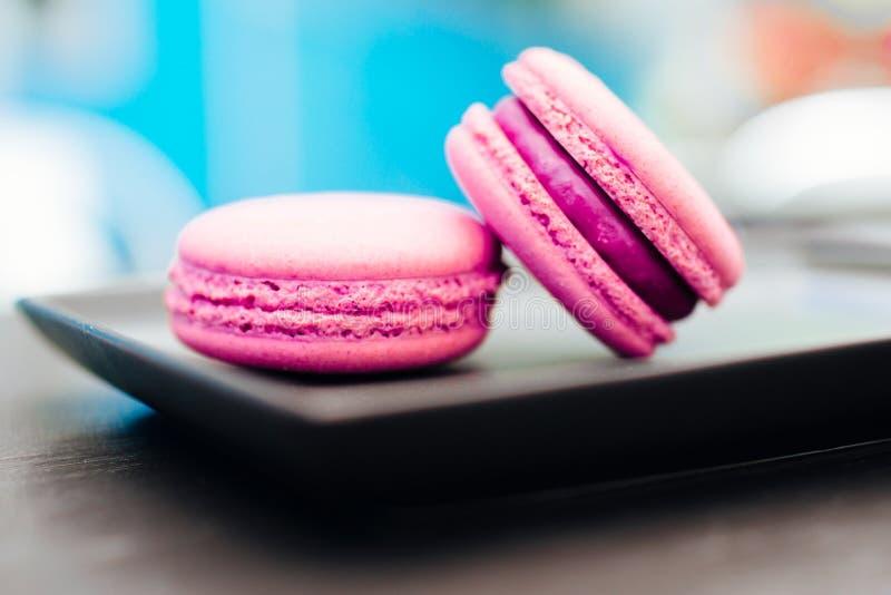 Bonbon, neue macarons mit Kaffee in einer blauen Schale auf einer schwarzen Tabelle lizenzfreies stockbild