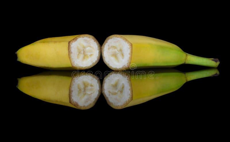 Bonbon, Schnitt in der halben Frucht einer gelben Banane mit einer hellen Reflexion im Glas stockbild