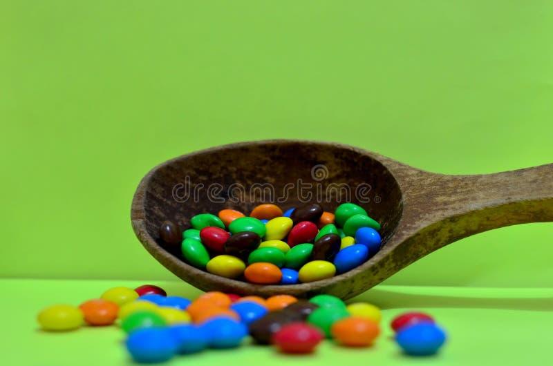 Bonbon sortierte mehrfarbige Schokoladen, Gummibälle in einem hölzernen Löffel auf einem grünen Photon oder Tabletten und Vitamin lizenzfreies stockbild