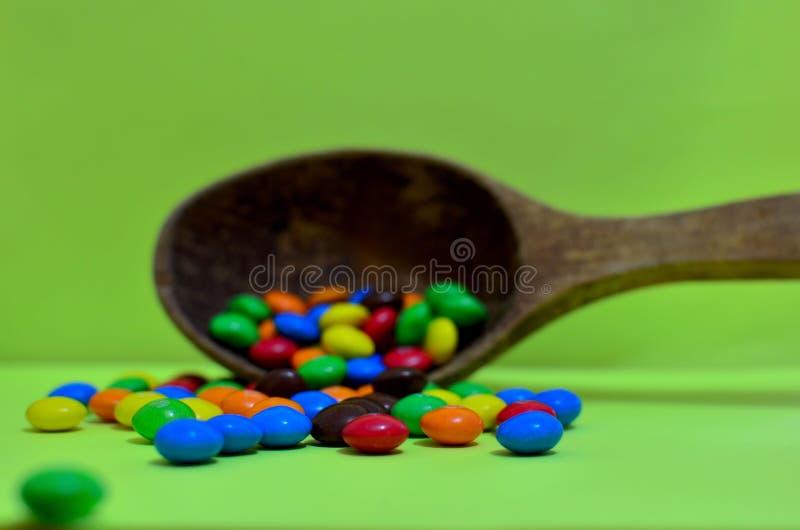 Bonbon sortierte mehrfarbige Schokoladen, Gummibälle in einem hölzernen Löffel auf einem grünen Photon oder Tabletten und Vitamin lizenzfreie stockfotografie