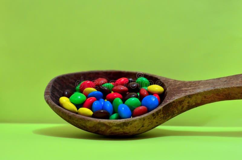Bonbon sortierte mehrfarbige Schokoladen, Gummibälle in einem hölzernen Löffel auf einem grünen Photon oder Tabletten und Vitamin lizenzfreie stockfotos