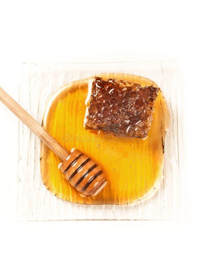 Bonbon und Bienenhonig in einer Platte lizenzfreies stockbild