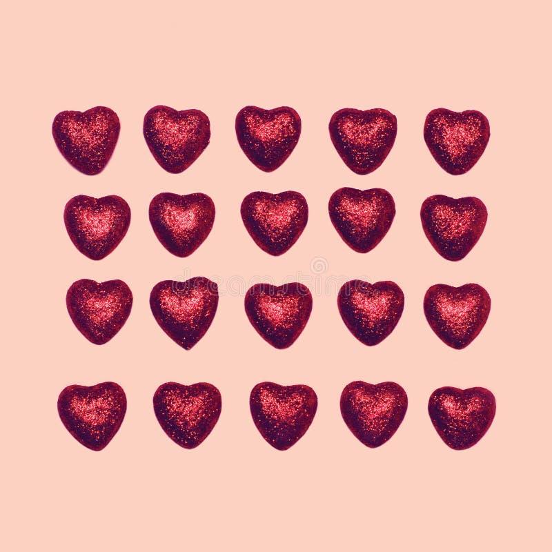 Bonbon viele roten dekorativen Süßigkeitsherzen lokalisiert auf rosa Hintergrund lizenzfreies stockbild