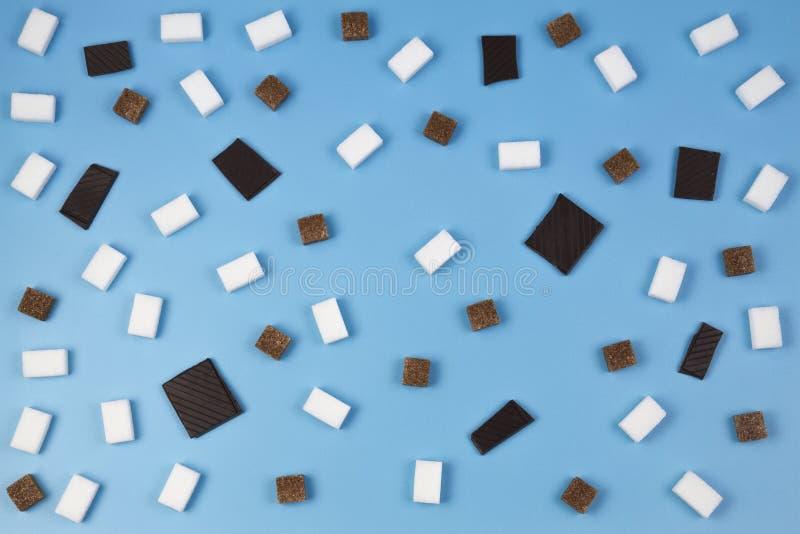 Bonbonmuster Würfel Browns und des raffinierten Zuckers und Schokoladenstücke auf blauem Hintergrund stockfotografie
