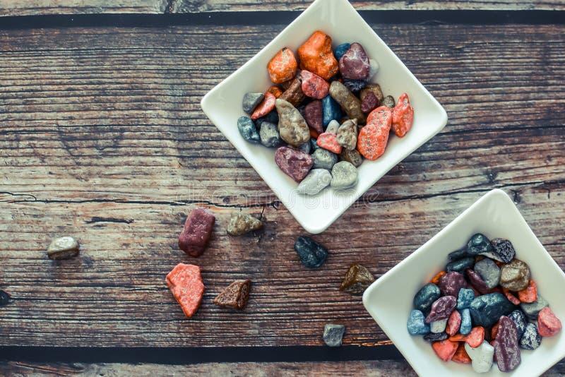 Bonbons au chocolat colorés doux, dans de petites cuvettes blanches, sur le fond en bois foncé image stock