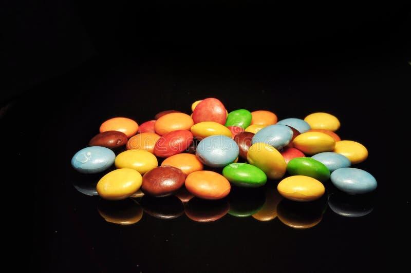Bonbons au chocolat color?s d'isolement sur le fond noir photo stock