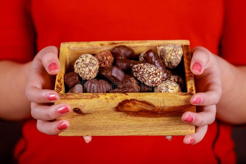Bonbons au chocolat dans la jeune participation gaie de fille de boîte-cadeau photo libre de droits