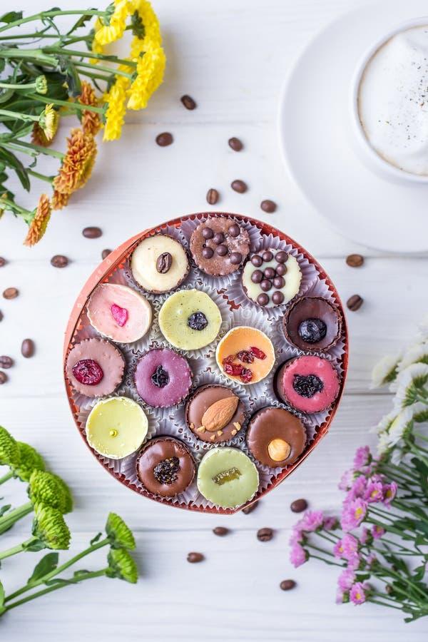 Bonbons au chocolat de luxe faits main dans un boîte-cadeau, un cappuccino de café et des chrysanthèmes multicolores sur en bois  images libres de droits