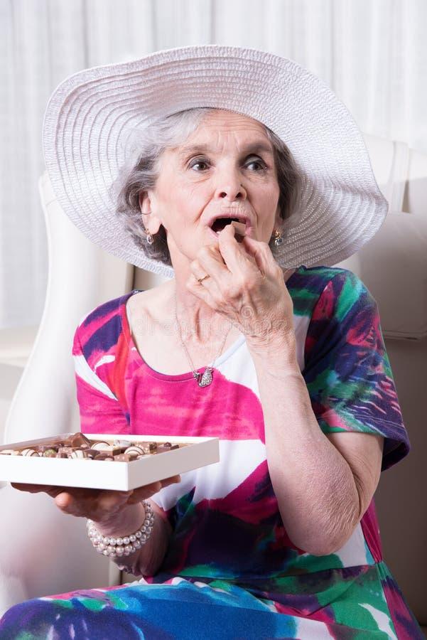 Bonbons au chocolat earing supérieurs femelles actifs photographie stock libre de droits
