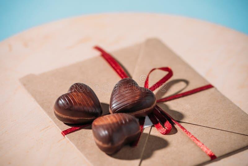 Bonbons au chocolat en forme de coeur sur l'enveloppe avec le ruban rouge, foyer sélectif avec l'espace de copie photo libre de droits