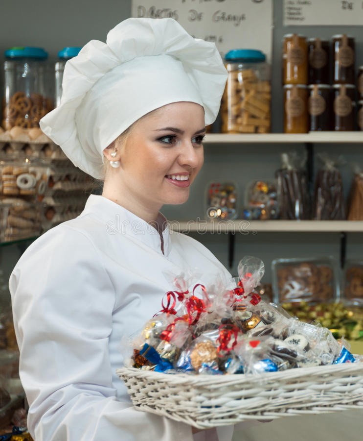 bonbons de offre à jeune vendeur féminin en confection locale photo stock