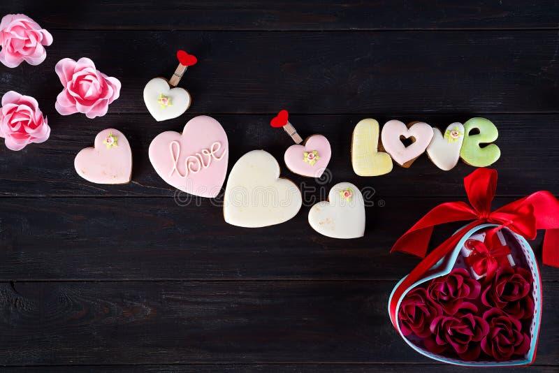 Bonbons le jour du ` s de Valentine Les biscuits dans la forme du coeur et de l'amour d'inscription, coeurs rouges ont formé et l image stock