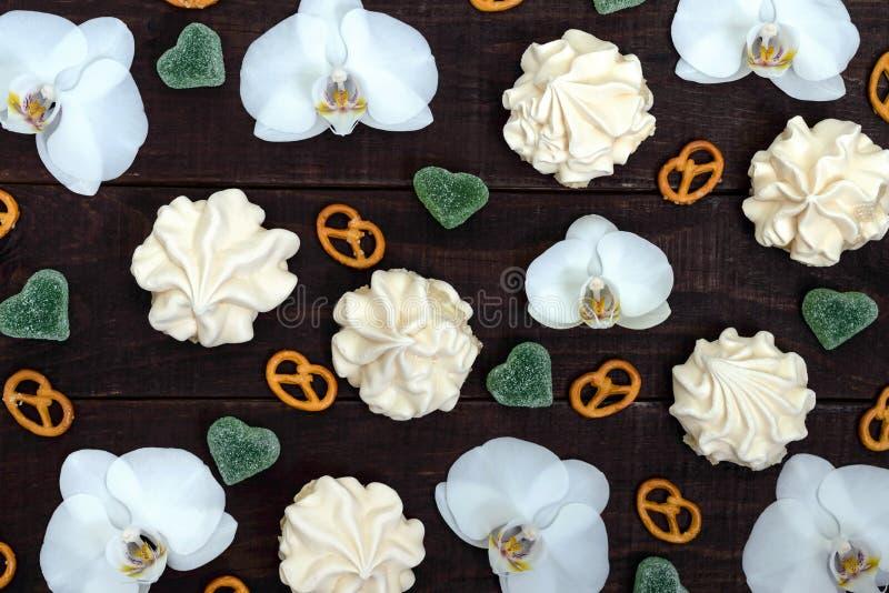 Bonbons: Meringen und Geleeherzen, weiße Orchidee blüht, salziges Bretzel auf einem dunklen hölzernen Brett stockbild