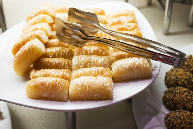 Bonbons orientaux présentés dans une rangée d'un plat, imbibé de le miel images stock