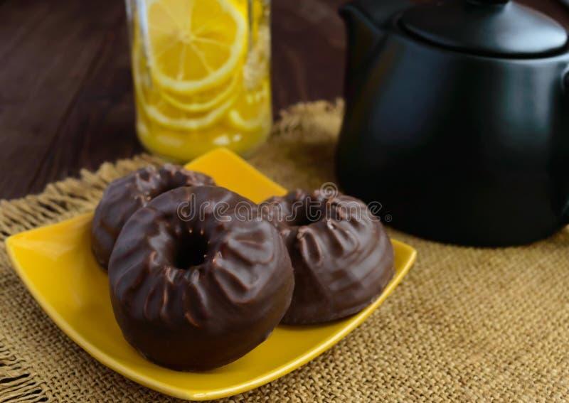 Bonbons: Zefir in der Schokolade und im Tee mit Zitrone auf hölzernem Hintergrund stockbild