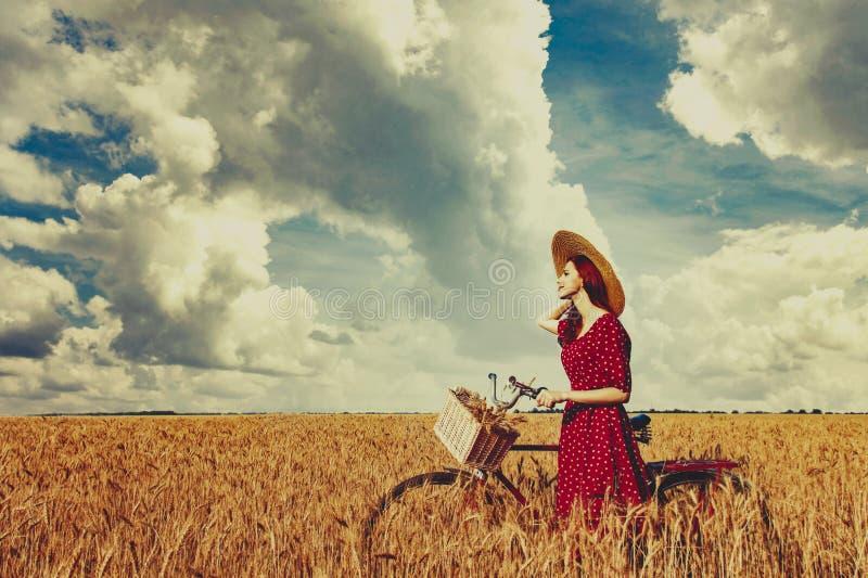 Bondaktig flicka med cykeln på vetefält arkivfoton