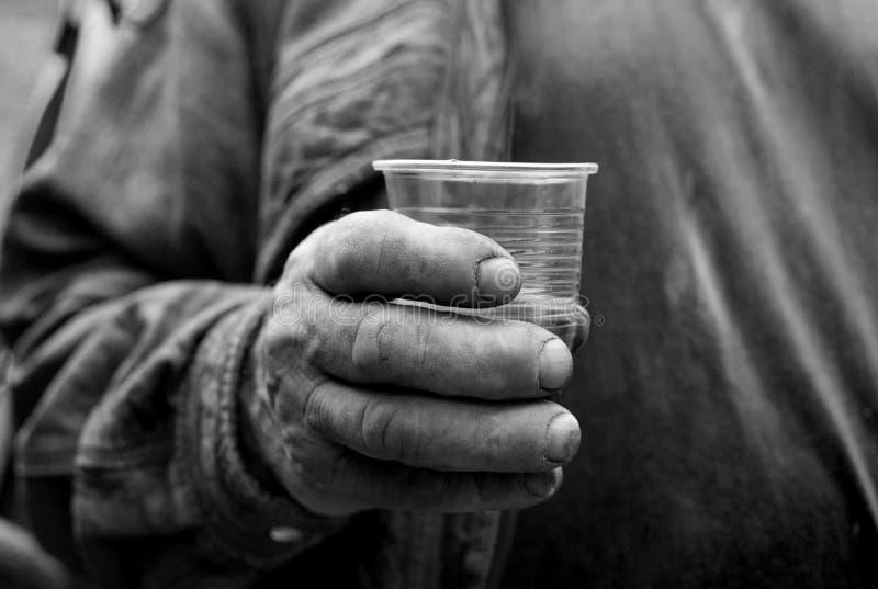 Bondaktig hand för ` s med plast- som dricker exponeringsglas royaltyfria bilder
