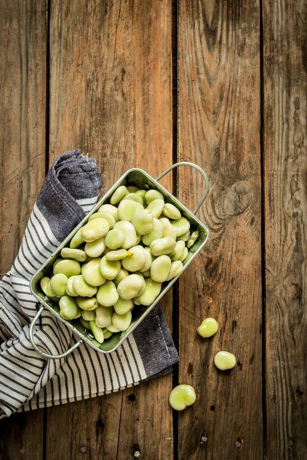 Bondbönor (bondbönor) på det trälantliga köksbordet royaltyfri fotografi