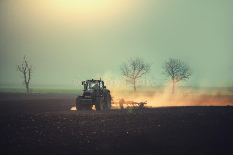 Bonde i traktoren som förbereder land med såbäddodlaren arkivfoto