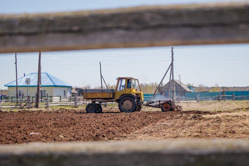 Bonde i traktoren som f?rbereder land med s?b?ddodlaren royaltyfri fotografi