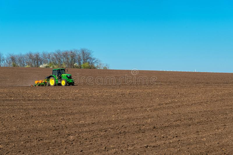 Bonde med att kärna ur för traktor - sådd kantjusterar på det jordbruks- fältet fotografering för bildbyråer