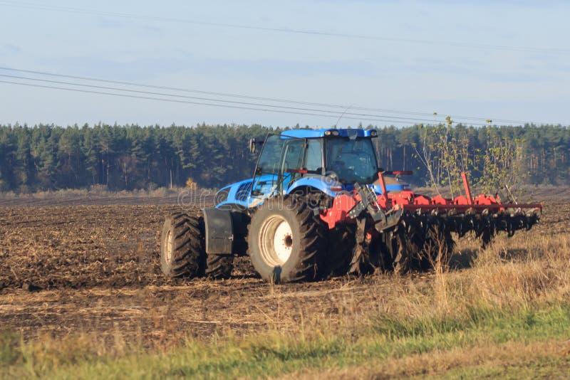 Bonde med att kärna ur för traktor - sådd kantjusterar på jordbruks- fält i vår arkivbild