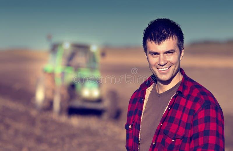 Bonde med traktoren på fält arkivbilder